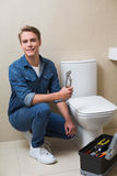Handsome plumber with toolbox doing toilet reparation Royalty Free Stock Photography