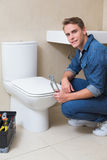 Handsome plumber with toolbox doing toilet reparation Stock Photo