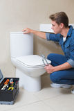Handsome plumber with toolbox doing toilet reparation Stock Images