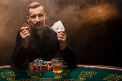 Handsome poker player with two aces in his hands and chips sitting at poker table in a dark room full of cigarette smoke. Cards, chips, whiskey, cigarettes stock photo