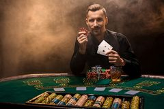 Handsome poker player with two aces in his hands and chips sitting at poker table in a dark room full of cigarette smoke. Cards, chips, whiskey, cigarettes royalty free stock image