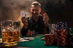 Handsome poker player with two aces in his hands and chips sitting at poker table in a dark room full of cigarette smoke. Cards, chips, whiskey, cigarettes royalty free stock photos