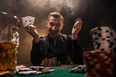 Handsome poker player with two aces in his hands and chips sitting at poker table in a dark room full of cigarette smoke. Cards, chips, whiskey, cigarettes royalty free stock images