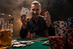 Handsome poker player with two aces in his hands and chips sitting at poker table in a dark room full of cigarette smoke. Cards, chips, whiskey, cigarettes royalty free stock photography