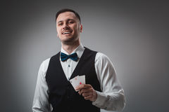 Handsome poker player with two aces in his hands. A man in the studio on a black-and-gray background royalty free stock photo