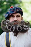 Handsome portrait of a brave Scot with a amazing beard and mustache curls in the Hungarian style. Royalty Free Stock Image
