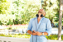 |Handsome posing with headphones and and a phone in his hand Royalty Free Stock Images