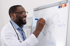 Handsome positive chemist writing a formula. Time for chemistry. Handsome positive male chemist smiling and looking at the whiteboard while writing a formula Stock Photos