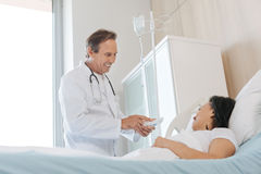 Handsome positive doctor talking to his patient Royalty Free Stock Image