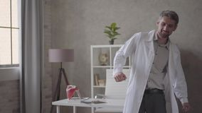 Handsome positive, successful and satisfied man in white robe dancing with x-ray in hands in modern clinic. The doctor stock video