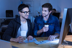 Handsome positive programmers enjoying their coffee. Tasty drink. Handsome positive programmers laughing and enjoying their coffee while sitting in front of the Stock Photos
