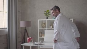 Handsome positive, successful and satisfied man in white robe dancing in the modern clinic office. Happy doctor got stock footage