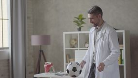 Handsome positive, successful and satisfied man in white robe playing with the ball in the modern clinic office. Happy stock footage