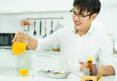 A handsome is pouring the orange juice to the glass royalty free stock photography