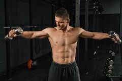 Handsome power athletic man bodybuilder doing exercises with dumbbell royalty free stock photo