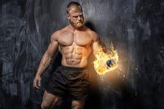 Handsome power athletic man bodybuilder. Fitness muscular body on dark background stock image