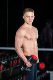 Handsome power athletic man with dumbbell confidently looking forward. Strong bodybuilder six pack, perfect abs Royalty Free Stock Photos