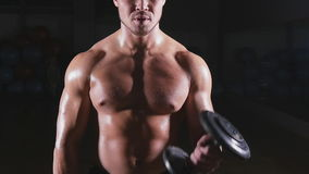 Handsome power athletic man with dumbbell