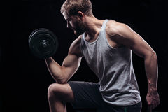 Handsome power athletic man with dumbbell. Handsome power athletic man with dumbbell confidently looking forward. Strong bodybuilder with six pack, perfect abs Stock Image