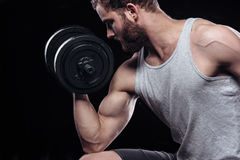 Handsome power athletic man with dumbbell. Handsome power athletic man with dumbbell confidently looking forward. Strong bodybuilder with six pack, perfect abs Royalty Free Stock Photos