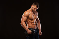 Handsome power athletic man with dumbbell is confidently looking forward. Strong bodybuilder with six pack, perfect abs. Shoulders, biceps, triceps and chest Royalty Free Stock Images
