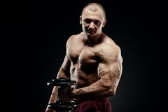 Handsome power athletic man in training pumping up muscles with Stock Images