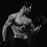 Handsome power athletic man in training pumping up muscles with Stock Photos