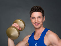 Handsome power athletic man in training pumping up muscles with dumbbells in a gym. Blue t-shirt Stock Photo