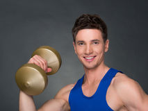 Handsome power athletic man in training pumping up muscles with dumbbells in a gym. Blue t-shirt Stock Photos