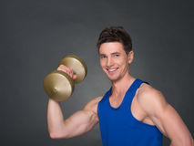 Handsome power athletic man in training pumping up muscles with dumbbells in a gym. Blue t-shirt Royalty Free Stock Photos