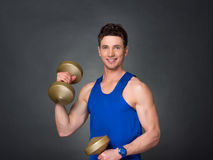 Handsome power athletic man in training pumping up muscles with dumbbells in a gym. Blue t-shirt Royalty Free Stock Image