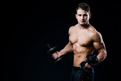 Handsome power athletic man training pumping up muscles with dumbbells in a gym. Fitness muscular body  on black. Man showing his six pack abs on dark background Stock Photos