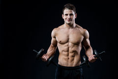 Handsome power athletic man training pumping up muscles with dumbbells in a gym. Fitness muscular body on black royalty free stock photos