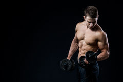 Handsome power athletic man training pumping up muscles with dumbbells in a gym. Fitness muscular body  on black. Man showing his six pack abs on dark background Stock Photo