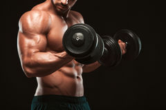 Handsome power athletic man in training pumping up muscles with dumbbells in a gym. Fitness muscular body isolated on. Dark background Stock Photo