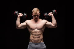 Handsome power man fitness-model with six packs is training with dumbbells,  on black background with copyspace Stock Photo