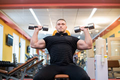 Handsome powerful athletic man doing barbell shoulder press exercise. Strong bodybuilder with perfect muscles. Royalty Free Stock Photos
