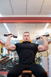 Handsome powerful athletic man doing barbell shoulder press exercise. Strong bodybuilder with perfect muscles. Royalty Free Stock Photography
