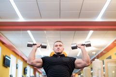 Handsome powerful athletic man doing barbell shoulder press exercise. Strong bodybuilder with perfect muscles. Handsome powerful athletic man doing barbell stock images