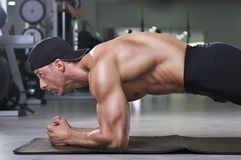 Handsome powerful athletic man doing plank exercise. Strong bodybuilder with perfect muscular abs, back and arms stock images