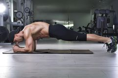 Handsome powerful athletic man doing plank exercise. Strong bodybuilder with perfect muscular abs, back and arms stock image