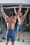 Handsome powerful athletic man doing pull-ups. Strong bodybuilder with perfect abs, back and chest. stock photo
