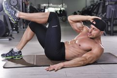 Handsome powerful athletic man performing crunches. Royalty Free Stock Image