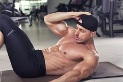 Handsome powerful athletic man performing crunches. stock photography