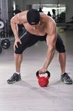 Handsome powerful athletic man performing kettle bell exercise. Royalty Free Stock Photography