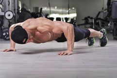Handsome powerful athletic man performing push ups at the gym. Royalty Free Stock Photos