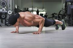 Handsome powerful athletic man performing push ups at the gym. stock photos