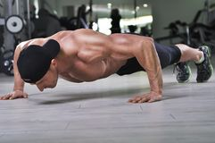 Handsome powerful athletic man performing push ups at the gym. royalty free stock images