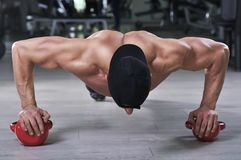 Handsome powerful athletic man performing push ups with kettle bell royalty free stock images