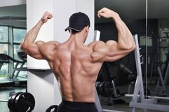 Handsome powerful athletic man posing at the gym. Royalty Free Stock Photo